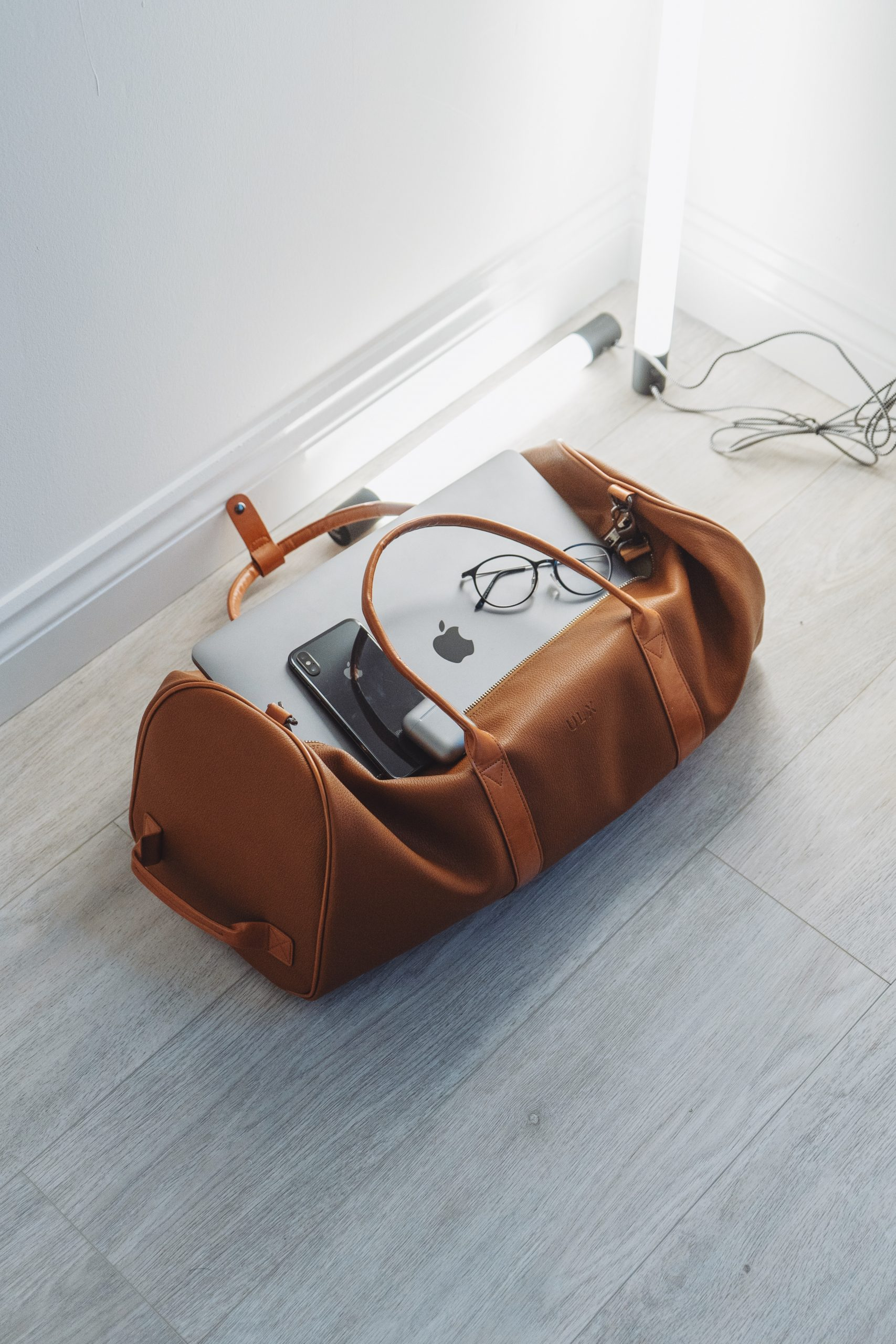 Leather carry on bag with glasses, laptop, and phone